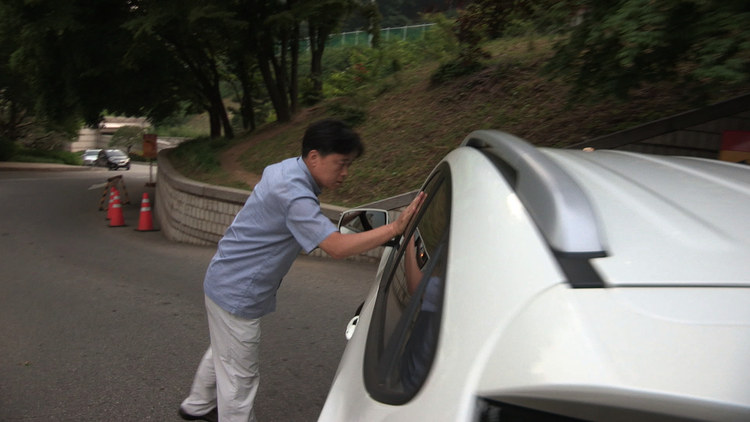 Director Choi Seung-ho stands in front of a car carrying National Intelligence Service officials to prevent them from leaving court without answering his questions.