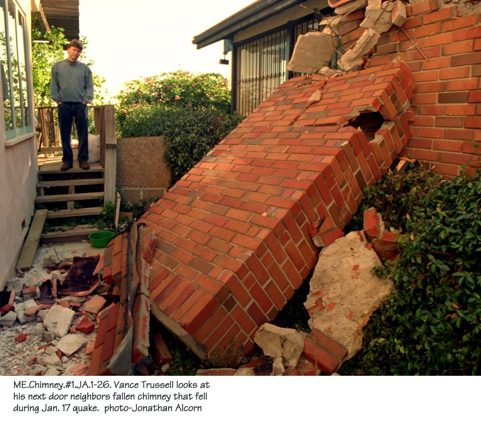 Vance Trussell looks at his next door neighbor's fallen chimney after the 1994 Northridge earthquake.