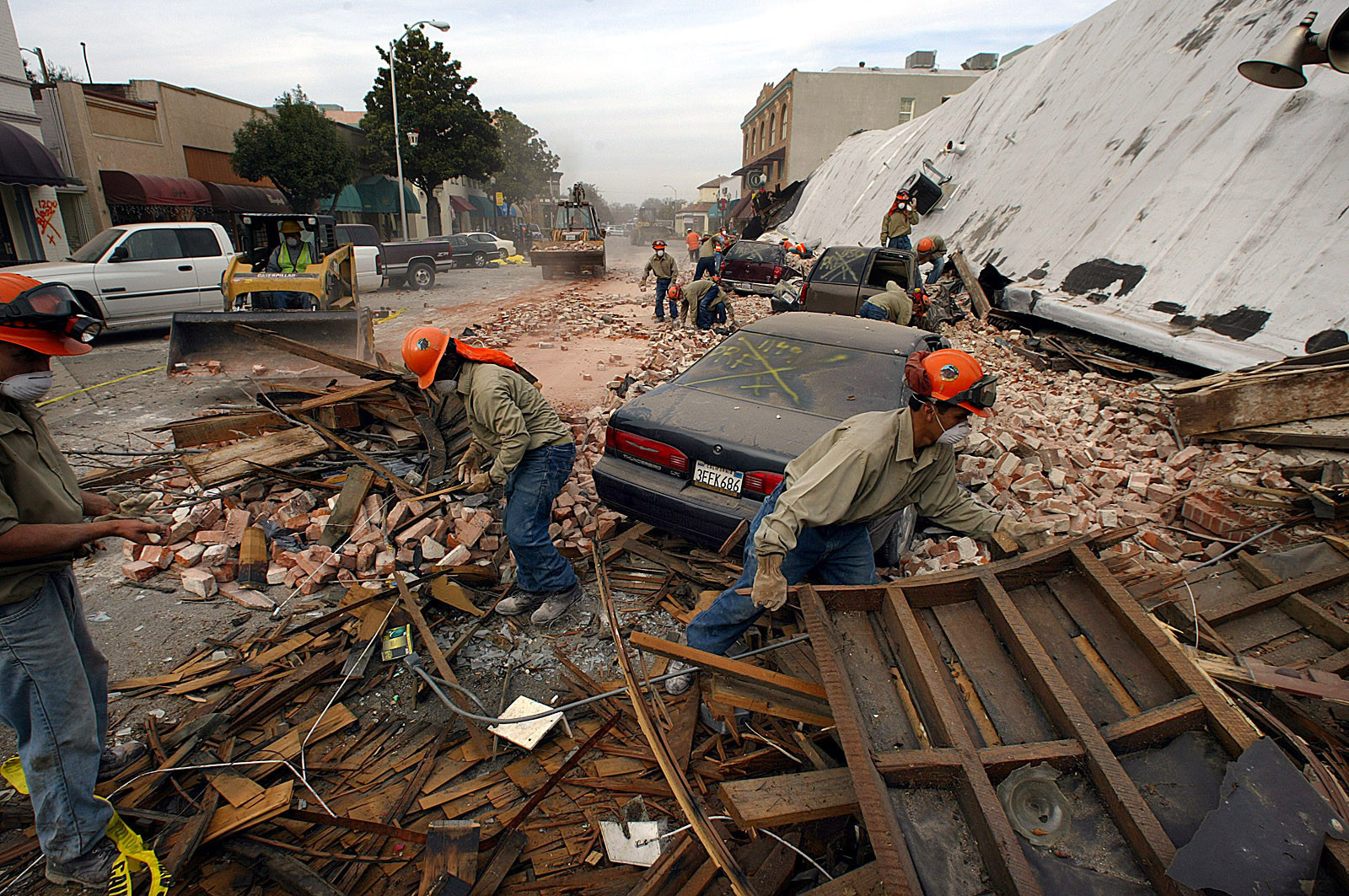 Rescue workers sift through the debris of an unretrofitted brick building in the wake of the 2003 Paso Robles earthquake. Two women who worked in the building died as they tried to flee.