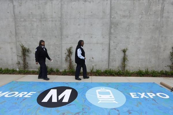 MTA drivers Sharie Byrd, left, and Carolyn Kelly walk past the banner they will hold as the first Metro Expo Line train arrives at the downtown Santa Monica station. (Genaro Molina / Los Angeles Times)