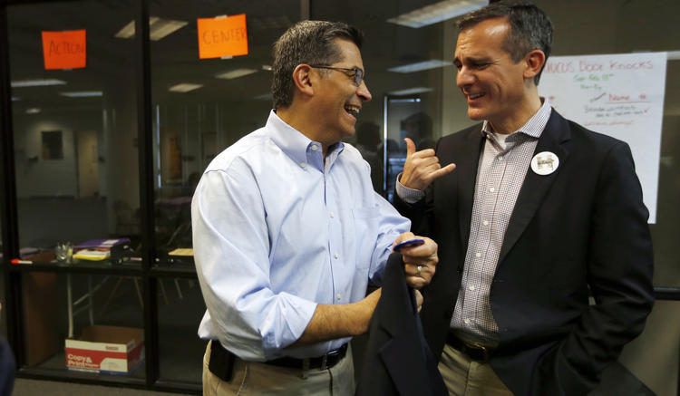 Two Hillary Clinton surrogates, U.S. Rep. Xavier Becerra, left, and Mayor Eric Garcetti, both of Los Angeles, meet before a Nevada rally for Clinton in February. (Francine Orr / Los Angeles Times)