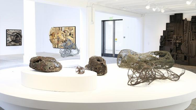 Claire Falkenstein sculptures, foreground, are shown with reliefs by Lee Bontecou, left rear, and Louise Nevelson, right rear, at Hauser Wirth & Schimmel.