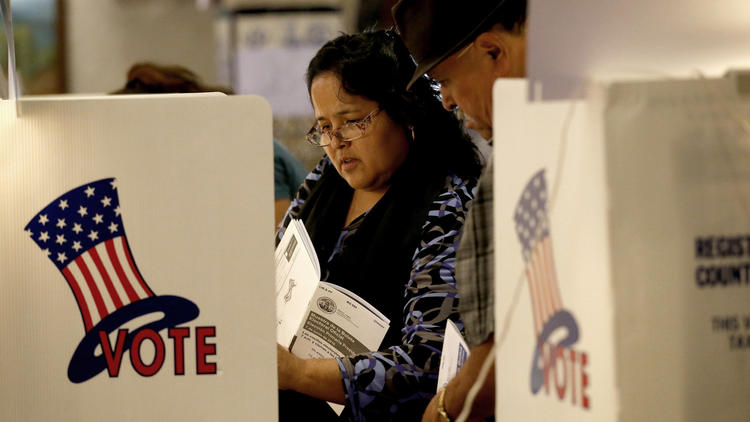 Jesus and Adriana Mata cast their ballots in the California primary election at a polling place inside the El Gallo restaurant in El Mercado de Los Angeles in Boyle Heights. (Allen J. Schaben / Los Angeles Times)