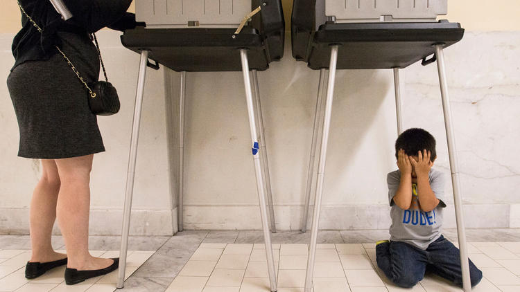 Johnny Lucero, 3, plays underneath a polling box while his mother, Nicanora Contreras, casts her vote Tuesday at San Francisco City Hall. (Jessica Christian/The San Francisco Examiner via AP)