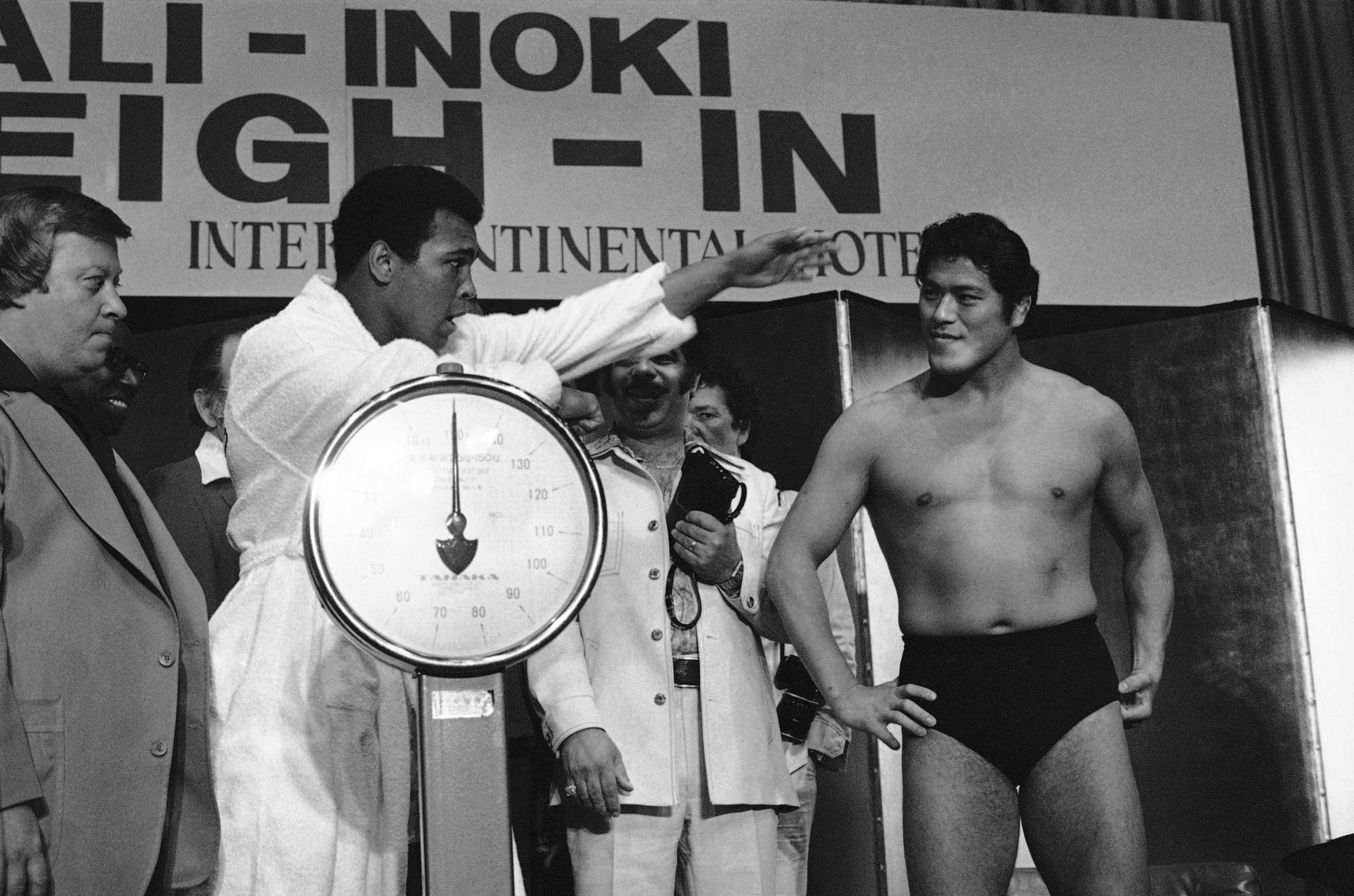 Muhammad Ali, standing on scale, gestures at his opponent, National Wrestling Federation world heavyweight champion Antonio Inoki.