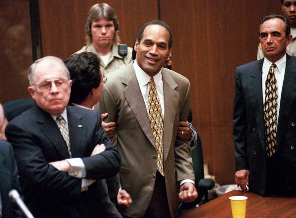 O.J. Simpson clenches his fists in victory on Oct. 3, 1995, after a Los Angeles jury found him not guilty of the slayings of his ex-wife, Nicole Brown Simpson, and her friend Ronald Goldman. (Myung Chun / Pool photo)