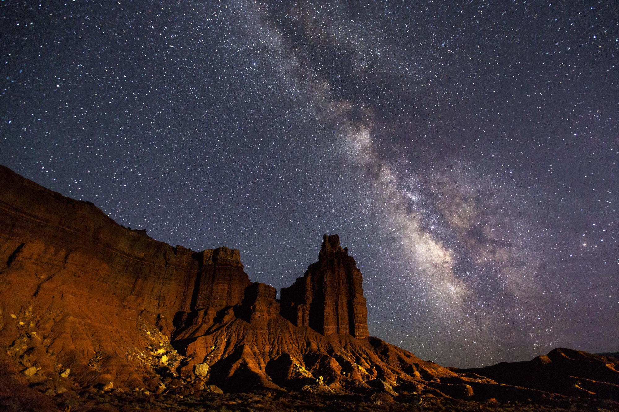 The Milky Way glimmers over Chimney Rock at Capitol Reef National Park, Utah.