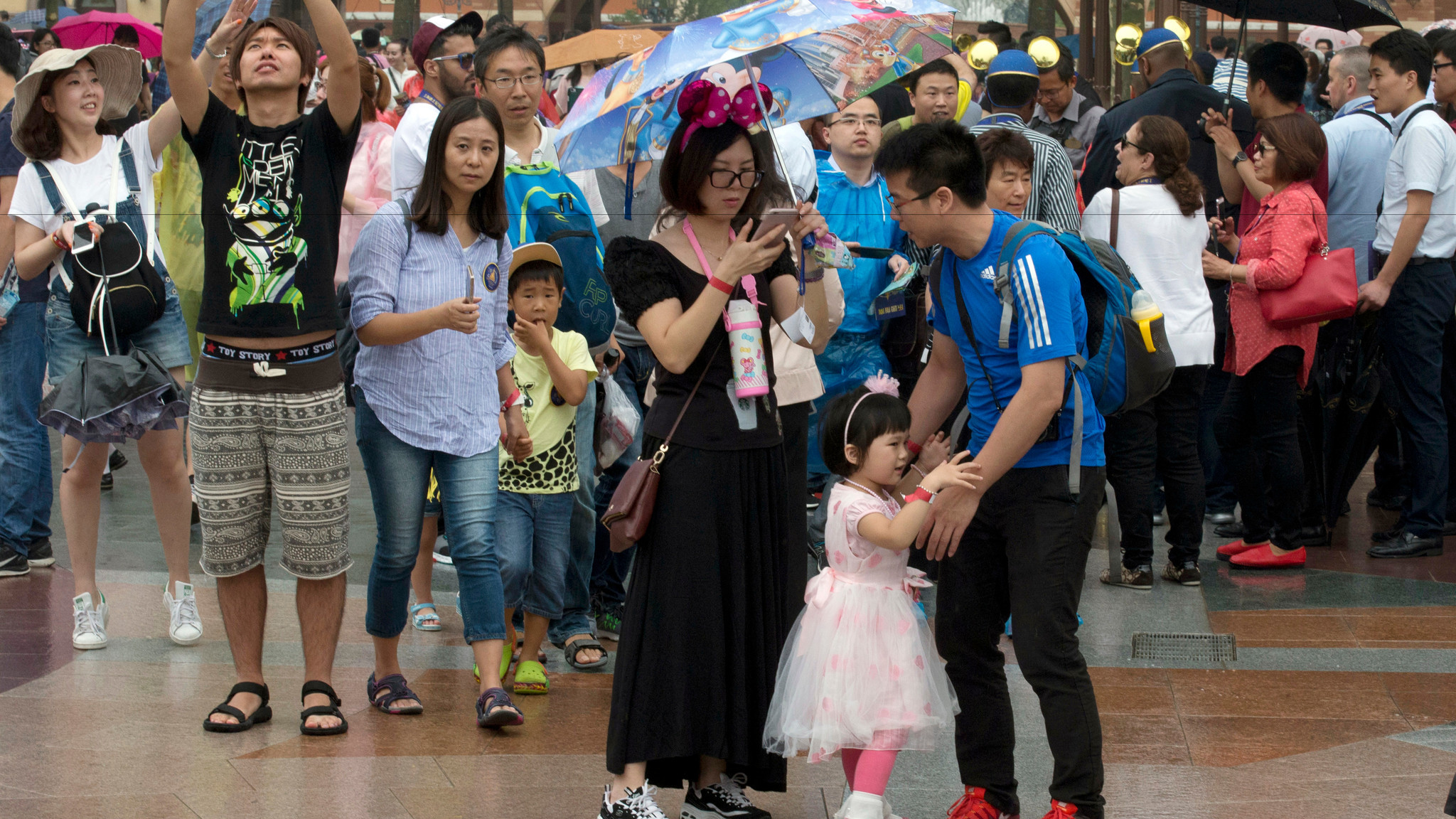 A child asks to be carried during a crowded opening day at the Disney Resort in Shanghai. (AP Photo/Ng Han Guan)