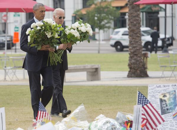 President Obama and Vice President Joe Biden place flowers for the shooting victims at a memorial at the Dr. Phillips Center for the Performing Arts in Orlando, Fla., on June 16, 2016. (SAUL LOEBSAUL/AFP/Getty Images)