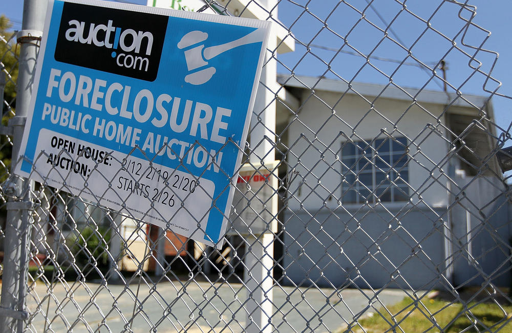 A foreclosure sign hangs on a fence in front of a foreclosed home in Richmond in 2011.