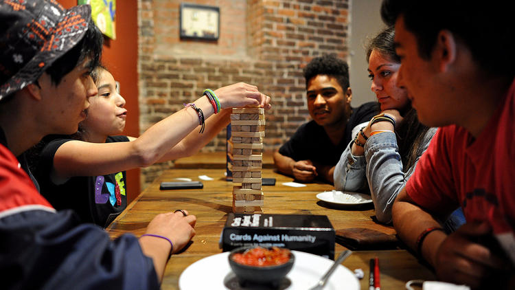A group of young people play Tumbling Tower at the GameHaus Cafe in Glendale.