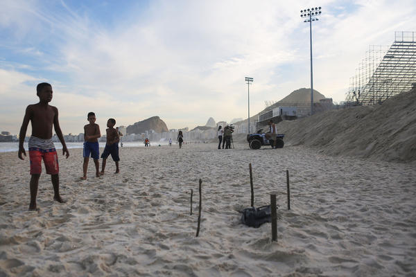 Young beachgoers walk near body parts, covered in a plastic bag, discovered on Copacabana Beach near the Olympic beach volleyball venue, top right, on Wednesday. (Mario Tama / Getty Images)