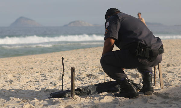 A police officer bends over human remains, covered in a plastic bag, discovered on Copacabana Beach near the Olympic beach volleyball venue on Wednesday. (Mario Tama / Getty Images)