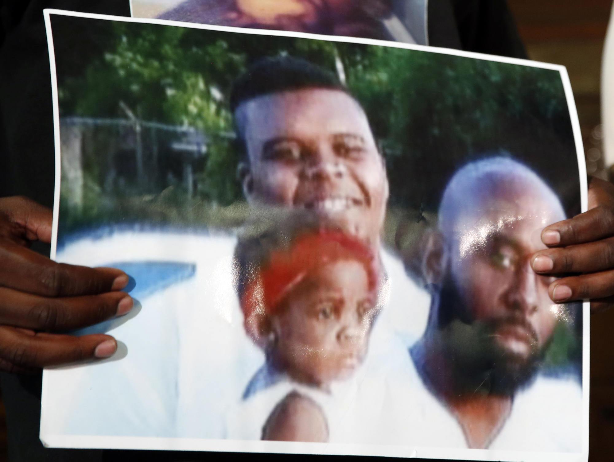 Michael Brown Sr. holds up a photo of himself, at right, his son, Michael Brown, top left, and a young child.