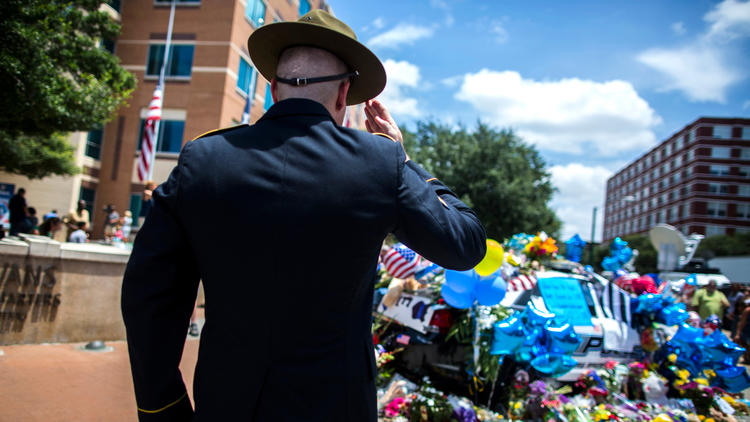 Retired Army Sgt. Chandler Davis pays his respects at a growing memorial in front of the Dallas police headquarters. (Barbara Davidson/Los Angeles Times)