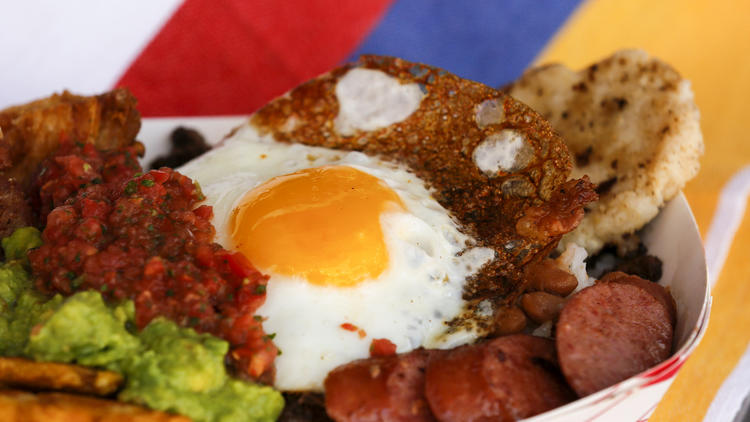 The Paisa Bowl is a protein-packed serving of pork belly, steak, sausage, beans, white rice, plantain, avocado, and an arepa topped with a fried egg, from the Cali Fresh food truck