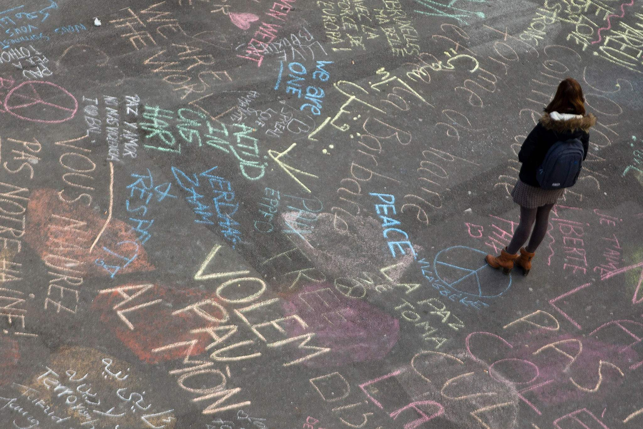 A woman reads messages written on the ground at a makeshift memorial on Place de la Bourse following attacks in Brussels.