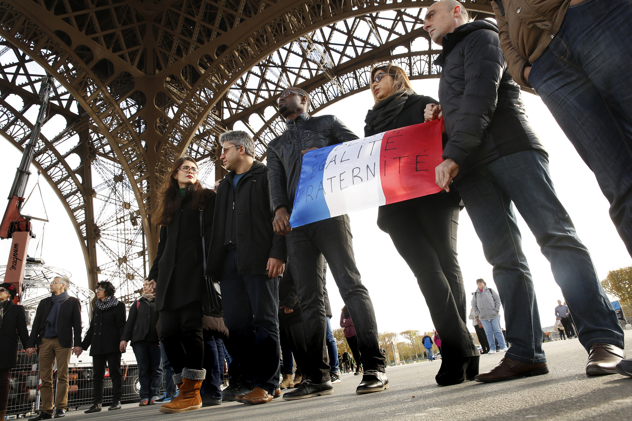 "Holding a French flag with the words ""Liberty, Equality, Brotherhood,"" participants stand united during a minute of silence under the Eiffel Tower  in observance of those who died during the terrorist attacks."