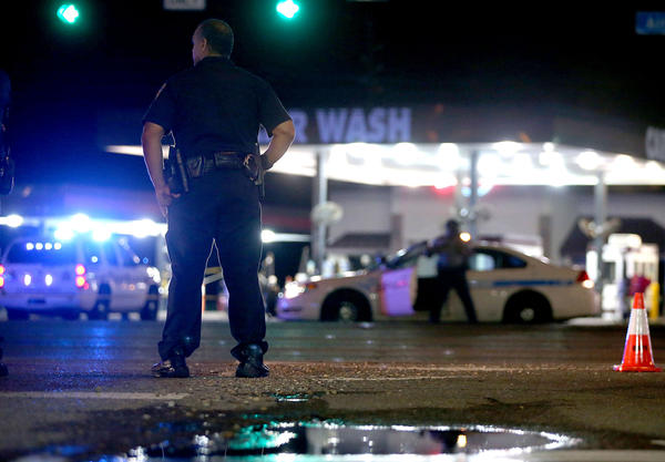 Police officers stand near the scene where three officers were killed on July 17 in Baton Rouge, La. (Sean Gardner / Getty Images)
