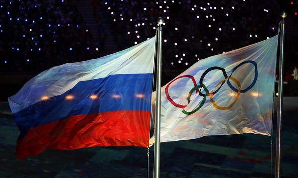 The Russian flag, left, and the Olympic flag fly during the closing ceremony of the 2014 Sochi Olympic Games. (Kay Nietfeld / EPA)