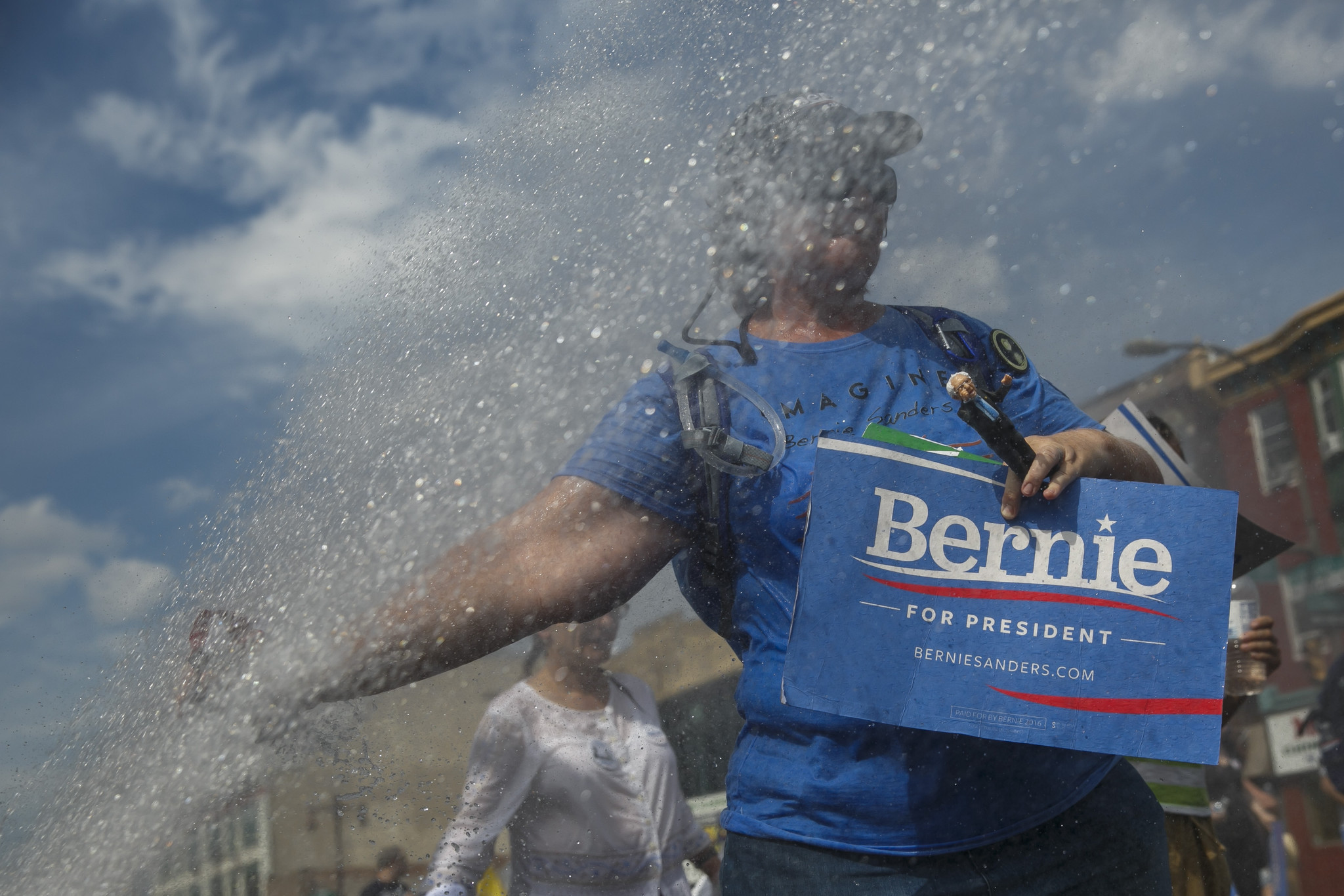 Bernie Sanders supporters walk past an open fire hydrant during Sunday's events in Philadelphia.