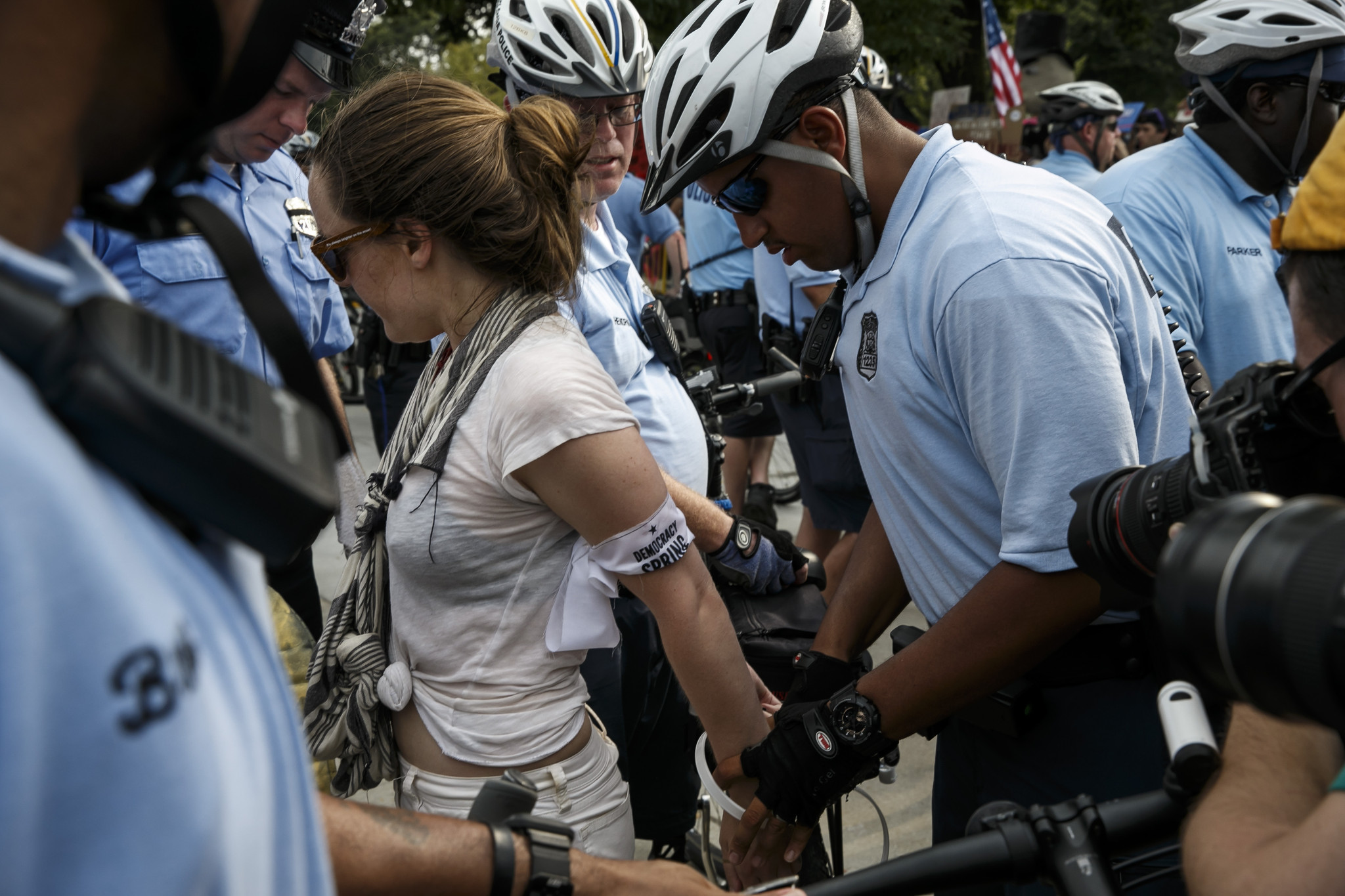 Protesters are detained and cited as they climb past a barrier set up by police at the Democratic National Convention