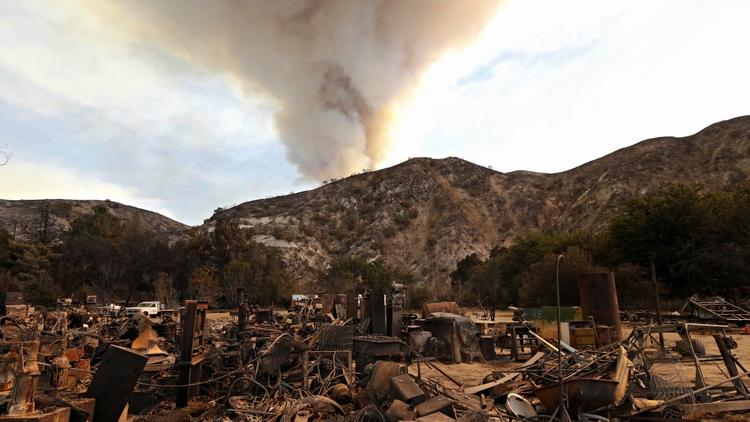 Remnants of a large machine shop that was destroyed in the fire as a plume builds in the mountains along Soledad Canyon Road near Acton on Monday. (Al Seib / Los Angeles Times)