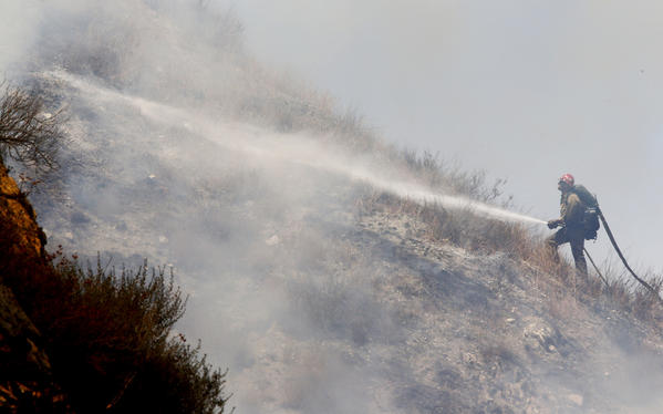 A firefighter battles a spot fire on Tuesday in rough terrain along Soledad Canyon Road. (Luis Sinco / Los Angeles Times)
