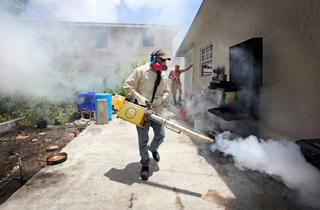 Carlos Varas, a Miami-Dade County mosquito control inspector, sprays pesticide to kill mosquitoes in Miami's Wynwood area.