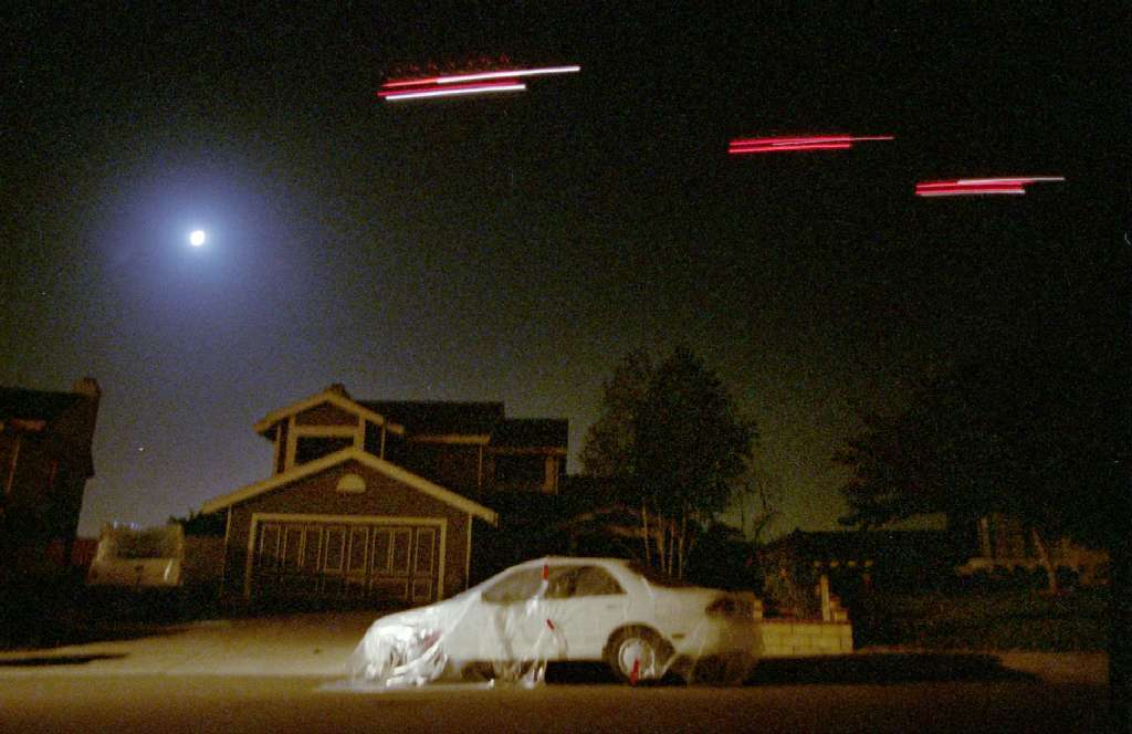 Helicopters cruise over the Camarillo neighborhood spraying malathion in 1994 to combat the first Medfly infestation in county history. Residents covered their cars with plastic tarps to avoid getting ruining the paint on their cars.