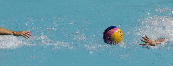 A Spanish and a U.S. player reach for the ball during Tuesday's opening-round women's water polo match. (Charlie Riedel / Associated Press)