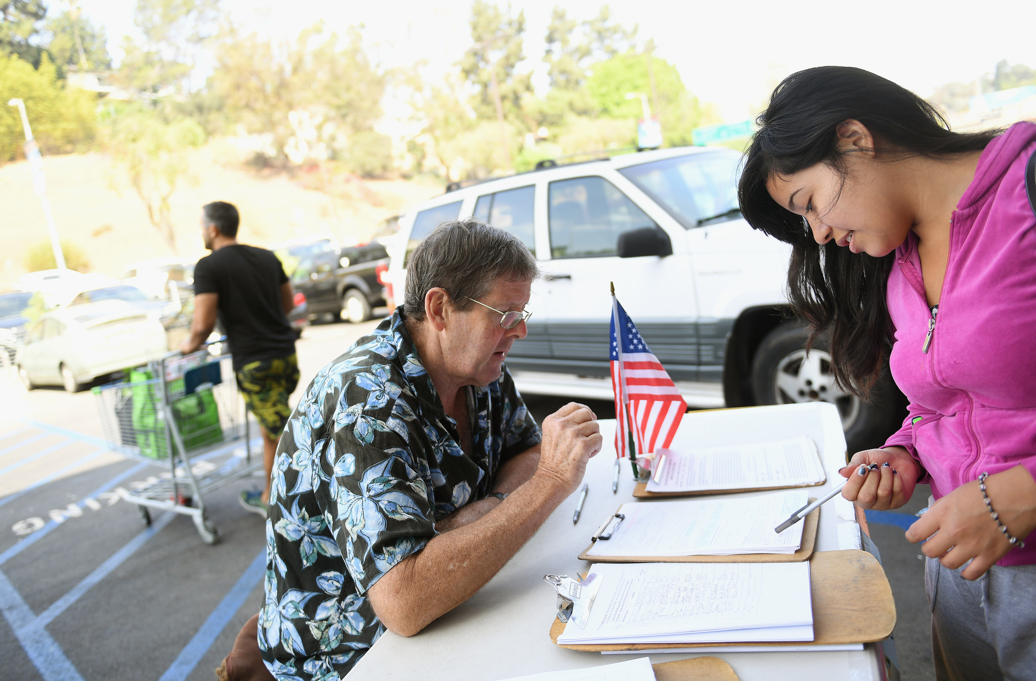 Tim Ecker collects signatures from Antonia Lopez, 19, in Silver Lake. Ecker says he made as much as $3,000 a week during peak season this year.