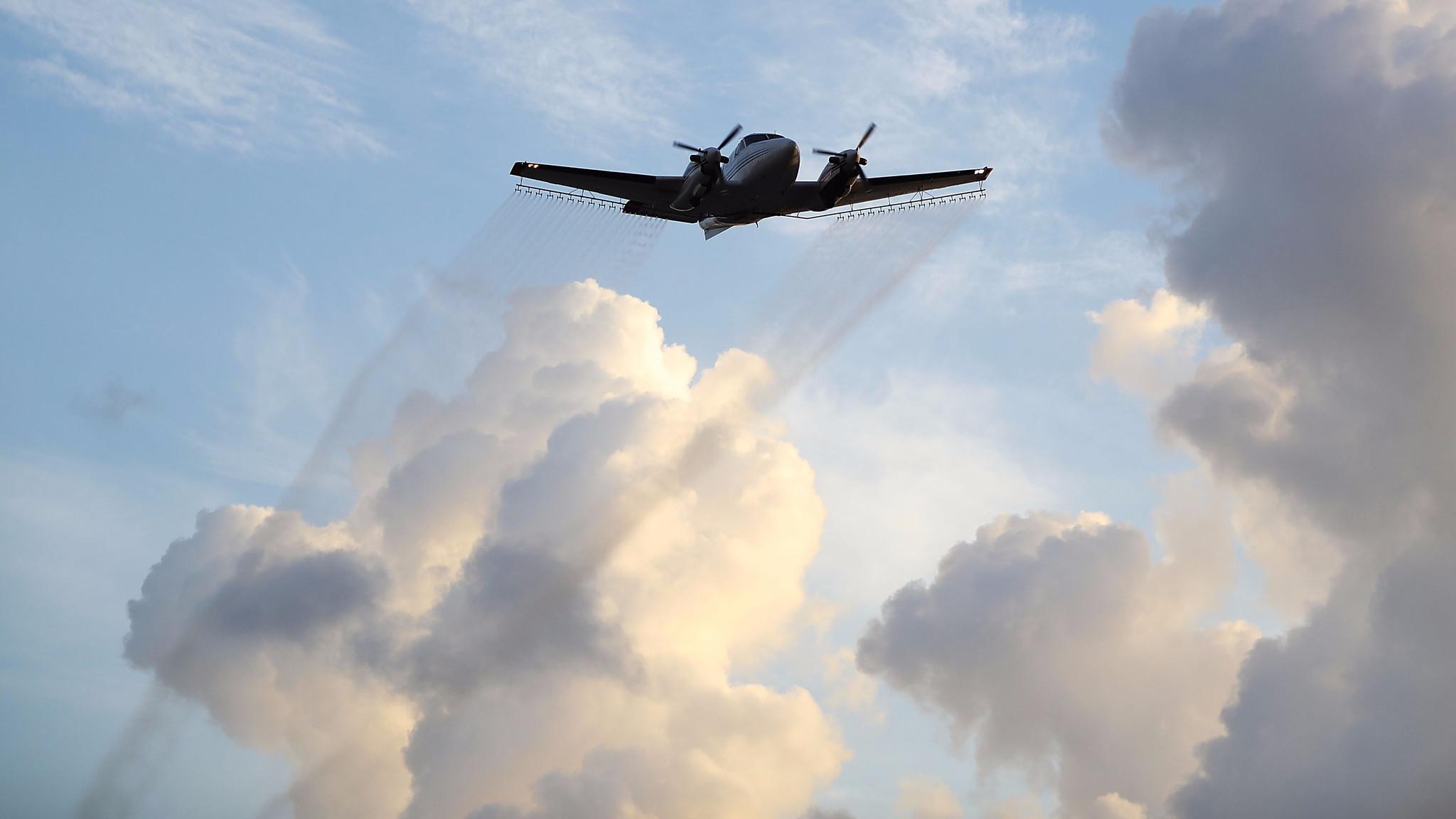 A plane sprays pesticide over the Wynwood neighborhood of Miami.