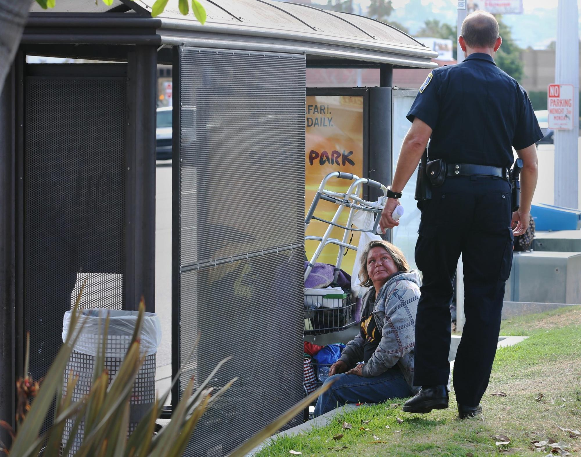 San Diego police Officer Brian Lucchesi, who works in homeless outreach, talks with a homeless woman in the Midway area about the assaults on homeless men.