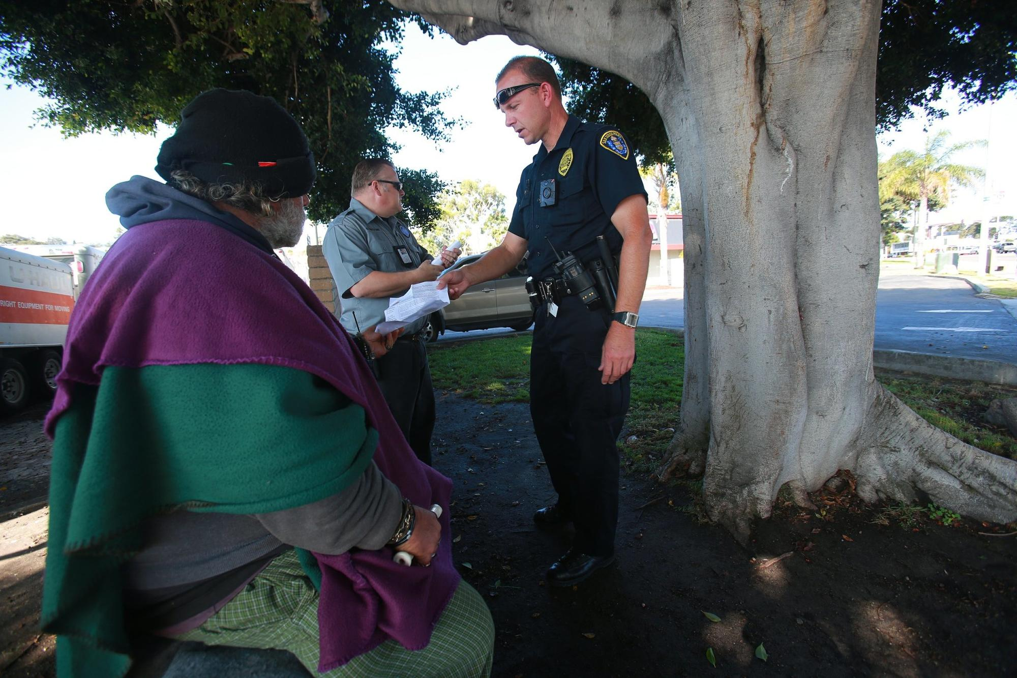HOT team officer Brian Lucchesi and PERT clinician Greg Whiteford, left, talk with people in the Midway area about the assaults on homeless people.