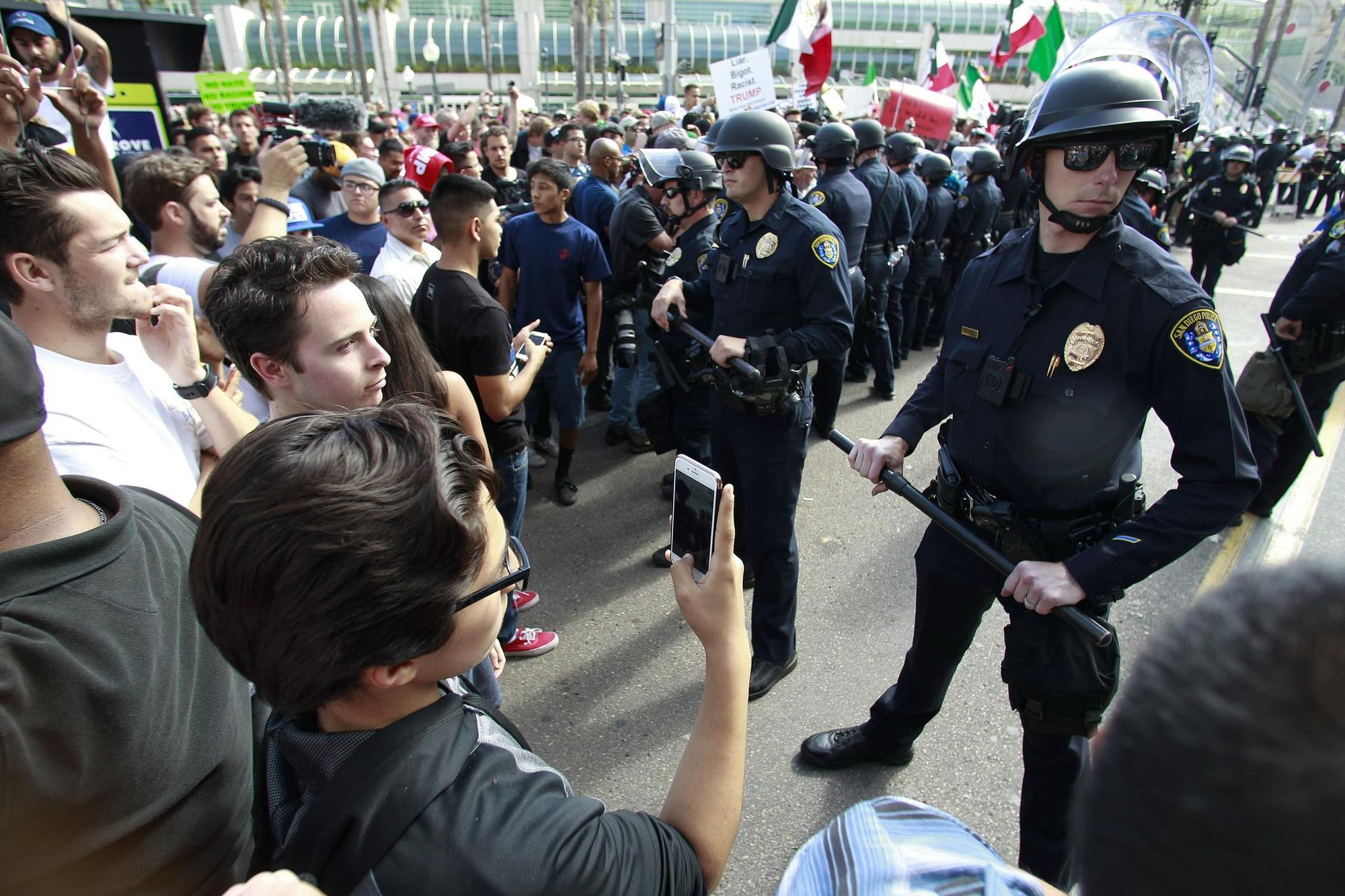 San Diego police officers get force full as they push protestors back during a protest in the Gaslamp Quarter.