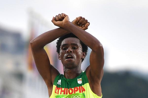 Ethiopia's Feyisa Lilesa crossed his arms above his head at the finish line (Olivier Morin / AFP/Getty Images)