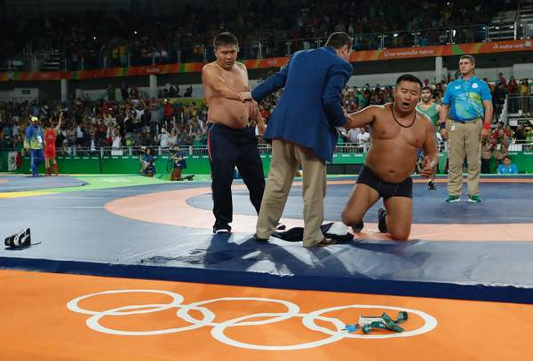 Mongolia wrestling coaches take off most of their clothes after wrestler Ganzorigiin Mandakhnaran lost his bronze medal match. (Jack Guez / AFP/Getty Images)