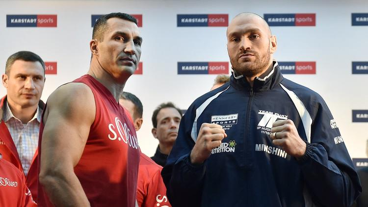 Challenger Tyson Fury, right, and world champion Wladimir Klitschko, left, stand on the podium after the Official Weigh-In in Essen, Germany, prior their heavyweight boxing fight, Friday, Nov. 27, 2015. The title clash will take place in Duesseldorf's LTU arena on Saturday. (AP Photo/Martin Meissne