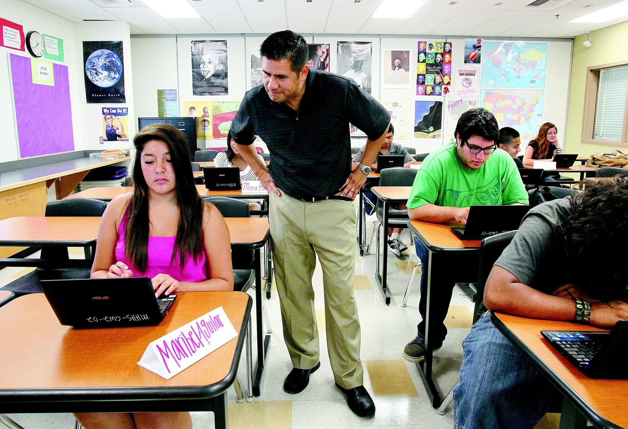 Teacher Paul Zendajas looks over the shoulder of student Maribel Aguilar on Wednesday in a California High School Exit Exam prep class at Mission Hills High School in San Marcos.
