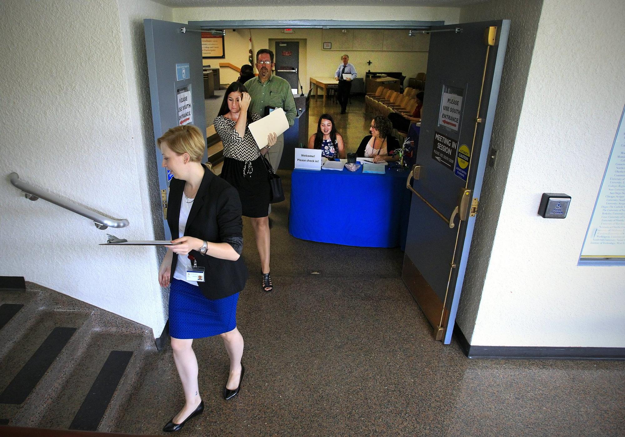 Erin Houston, left, a San Diego Unified School District human resources officer, leads a group of prospective teachers to her office for interviews during a job fair at the dist