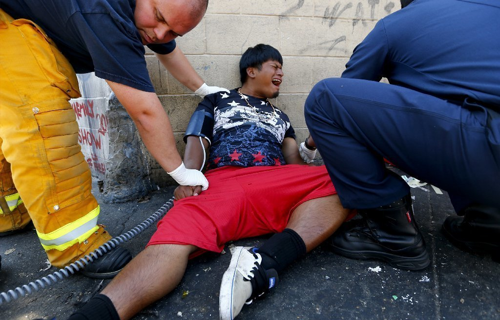 Safety officials assist a man on downtown L.A.'s skid row last week. (Luis Sinco / Los Angeles Times)