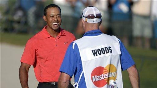 Tiger Woods, left, celebrates with his caddie Joe LaCava after winning the Arnold Palmer
