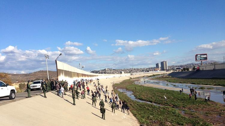 Border Patrol agents respond to a crowd one-eighth of a mile north of the U.S.-Mexico border in the Tijuana River channel. / U.S. Customs and Border Protection photo