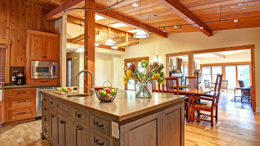 A focal point in the remodeled kitchen is a large island of gray-stained cherry wood with a concrete countertop.