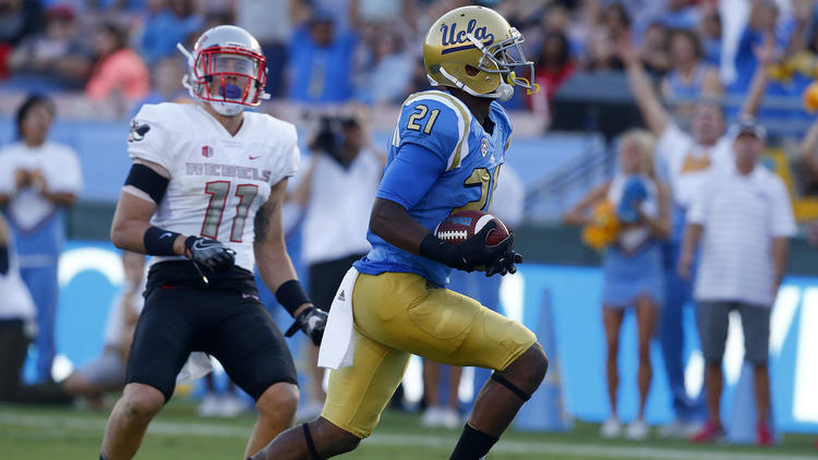 UCLA wide receiver Mossi Johnson beats UNLV defensive back Troy Hawthorne into the end zone in the second quarter. (Luis Sinco / Los Angeles Times)