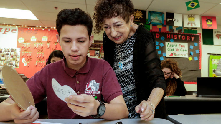 Gabriella Karin works with student Jason Orellana on an art project inspired by her life during World War II.