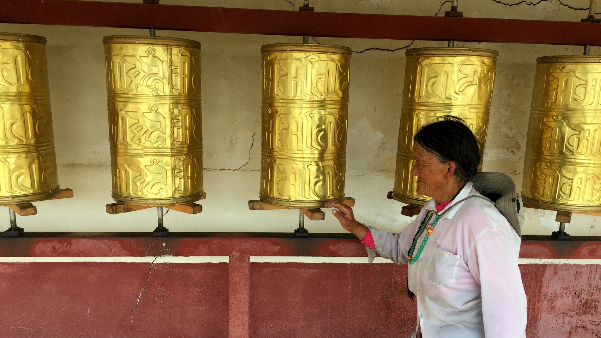 A Tibetan woman spins prayer wheels at a roadside tourist attraction in Aba prefecture.