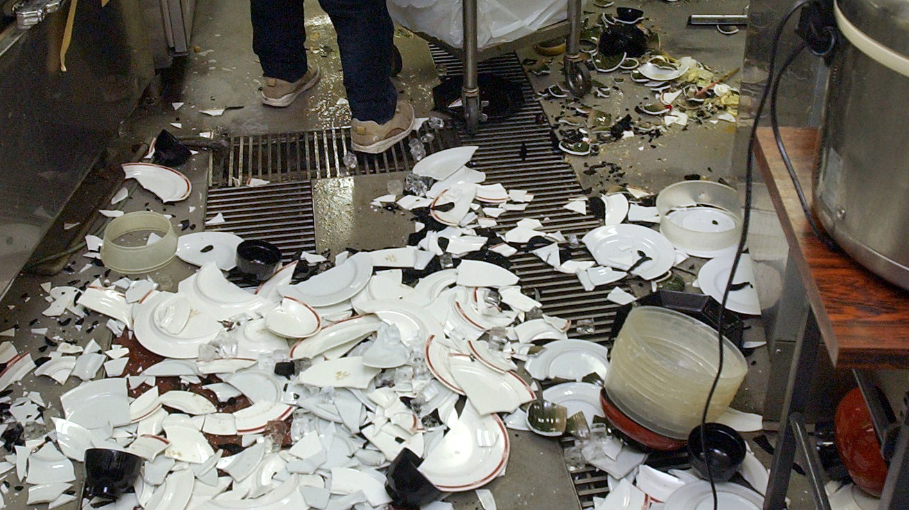 Workers clean up broken dishes at a restaurant in Kushiro, on the northern Japanese island of Hokkaido, after a powerful earthquake on Nov. 29, 2004.