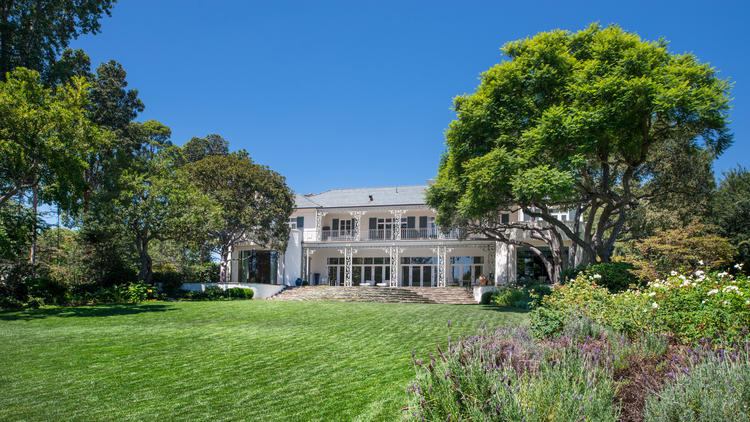 The Georgian Colonial mansion, designed by Gordon Kaufmann and built in 1938, sits on more than four park-like acres in Holmby Hills.